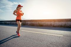 An asian woman athletic is jogging on the concrete road stock images