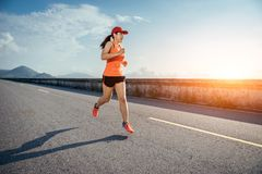 An asian woman athletic is jogging on the concrete road stock photo