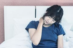 Beautiful Attractive Asian woman wearing white shirt sitting on bed royalty free stock image