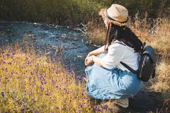 Asian woman backpacker sitting on flower field in forest background. Relax time on holiday ,selective and soft focus,tone of hipster style Royalty Free Stock Image