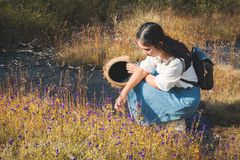 Asian woman backpacker sitting on flower field in forest background royalty free stock photography