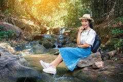 Asian woman backpacker sitting on the rock near waterfall in forest background. Relax time on holiday ,selective and soft focus,tone of hipster style Royalty Free Stock Image