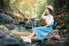 Asian woman backpacker sitting on the rock near waterfall in forest background. Relax time on holiday ,selective and soft focus,tone of hipster style Stock Photo
