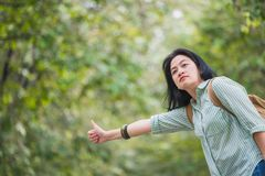 Asian woman backpacker standing on countryside road with tree in Royalty Free Stock Photography
