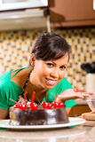 Asian woman baking  chocolate cake in kitchen. Asian woman presenting homemade chocolate cake with cherries she baked in her kitchen for dessert Royalty Free Stock Image