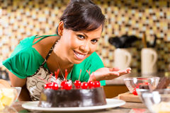 Asian woman baking  chocolate cake in kitchen. Asian woman presenting homemade chocolate cake with cherries she baked in her kitchen for dessert Royalty Free Stock Photos