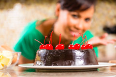 Asian woman baking  chocolate cake in kitchen. Asian woman presenting homemade chocolate cake with cherries she baked in her kitchen for dessert Stock Image