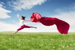 Asian woman ballerina holding red fabric making a big jump on blossom meadow. royalty free stock images