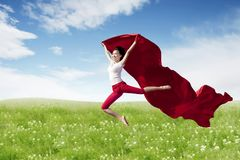 Asian woman ballerina holding red fabric making a big jump on blossom meadow. stock photos