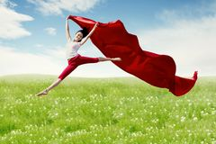 Asian woman ballerina holding red fabric making a big jump on blossom meadow. royalty free stock photos