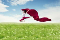 Asian woman ballerina holding red fabric making a big jump on blossom meadow. stock photography