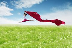 Asian woman ballerina holding red fabric making a big jump on blossom meadow. stock image
