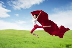 Asian woman ballerina holding red fabric making a big jump on green meadow. stock photos