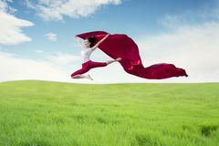 Asian woman ballerina holding red fabric making a big jump on meadow. royalty free stock photo