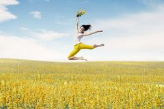Asian woman ballerina holds bouquet of flowers making a big jump on meadow. stock photo