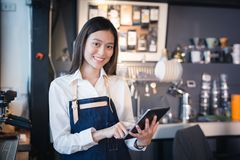 Asian woman barista smiling with tablet in her hand,Female employees are taking orders from online customers royalty free stock photo