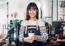 Asian woman barista wear jean apron holding hot take away coffee. Cup served to customer with smiling face at bar counter.cafe restaurant service concept Royalty Free Stock Photo
