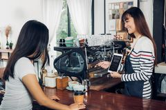 Asian woman barista wear jean apron suggestion coffee menu to cu. Asian women barista wear jean apron suggestion coffee menu to customer at bar counter with Stock Photo