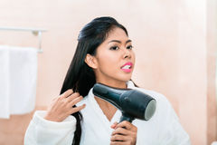 Asian woman in bathroom drying hair Royalty Free Stock Images