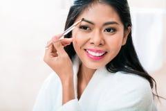 Asian woman in bathroom plucking eyebrows Stock Photo