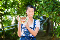 Asian Woman with Bavarian gingerbread heart. Young Asian woman in traditional Bavarian clothes or tracht with a gingerbread souvenir heart in beergarden on Stock Image