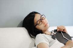 Asian woman be sleep with alarm clock on a bed. royalty free stock image