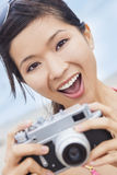 Asian Woman at Beach Taking Photograph With Camera Royalty Free Stock Photos