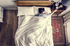 Asian woman on the bed waking up by the alarm clock Royalty Free Stock Images