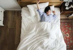Asian woman on the bed waking up in the morning Royalty Free Stock Image