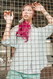 Asian woman behind a metal fence Royalty Free Stock Photography
