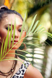 Asian woman behind palm leaf Royalty Free Stock Images