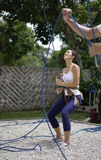 Asian Woman in belaying stance in outdoor rockclimb Stock Photos