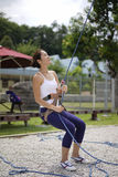 Asian Woman in belaying stance in outdoor rockclimb Stock Images