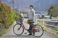 Asian woman and bicycle. Asian woman standing beside bicycle on the small road Royalty Free Stock Images