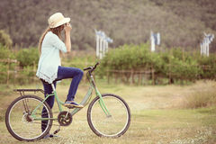 Asian woman on bicycle taking photo Stock Photography