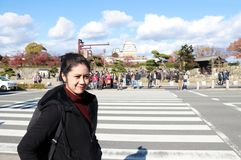 Asian woman in black clothing standing beside the road and crosswalk with out focus tourist. stock photography