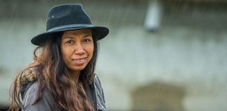 Asian woman with black hat and parka standing in the rain smiling stock photos
