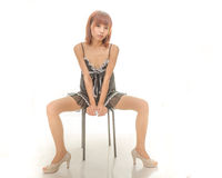 Asian woman in black and white underwear sitting on stool Stock Photo