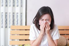 Asian woman blowing her nose while sitting on bed. illness woman. Sneezing in a tissue Stock Photos