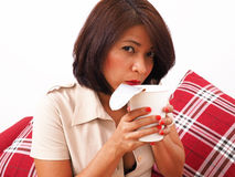Asian woman blows on foam cup Stock Images