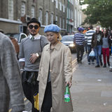 An Asian woman in a blue beret and raincoat with a Chinese man in a hat and sunglasses walking on Brick Lane Royalty Free Stock Image