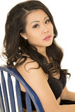 Asian woman on a blue chair close looking Stock Image
