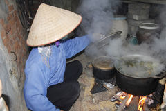 Asian woman boiling rice cake Royalty Free Stock Photo