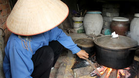 Asian woman boiling rice cake Stock Photos