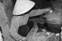 Asian woman boiling rice cake Stock Images