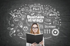 Asian woman with book and business strategy. Portrait of an Asian woman with glasses reading a book near a blackboard with a business strategy sketch on it Royalty Free Stock Photos