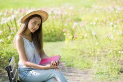 Asian woman with book in flower garden. Portrait of Happy beautiful Asian woman with hat holding book to read and enjoying life in the field with flowers in Stock Photography