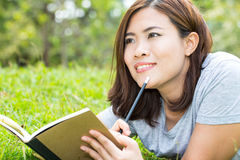 Asian woman with a book in the garden Stock Photo