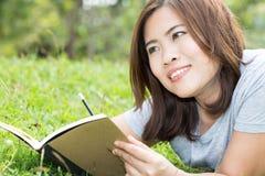 Asian woman with a book in the garden Royalty Free Stock Photos