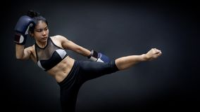 Asian woman boxer with boxing gloves kicking stock photography